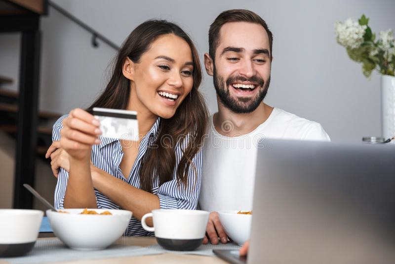 Coppie multietniche felici che mangiano prima colazione fotografie stock