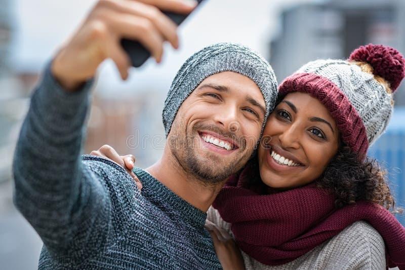 Coppie multietniche sorridenti che prendono selfie nell'inverno immagini stock libere da diritti