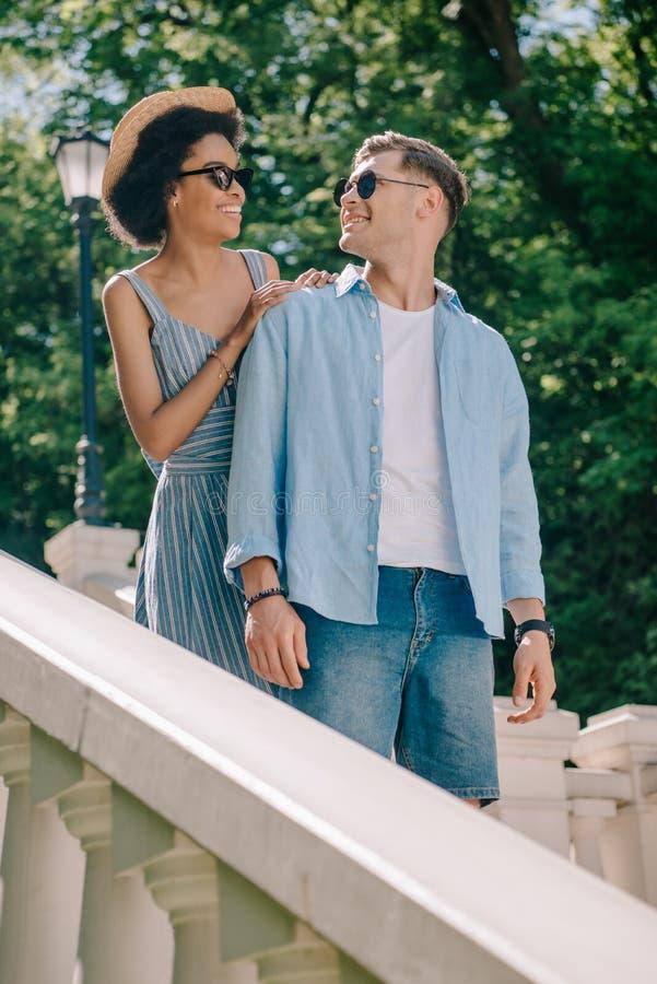 coppie multietniche sorridenti in occhiali da sole che stanno sulle scale immagine stock