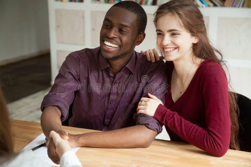 Coppie multirazziali attraenti felici che stringono le mani con il consulente o immagine stock