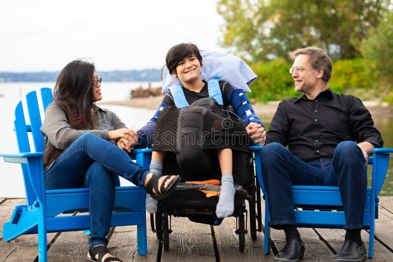 Coppie multirazziali con il ragazzo disabile nell'aria aperta della sedia a rotelle dalla l immagine stock