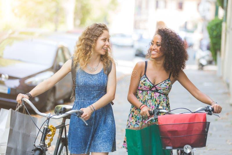 Coppie multirazziali degli amici con le bici fotografie stock libere da diritti