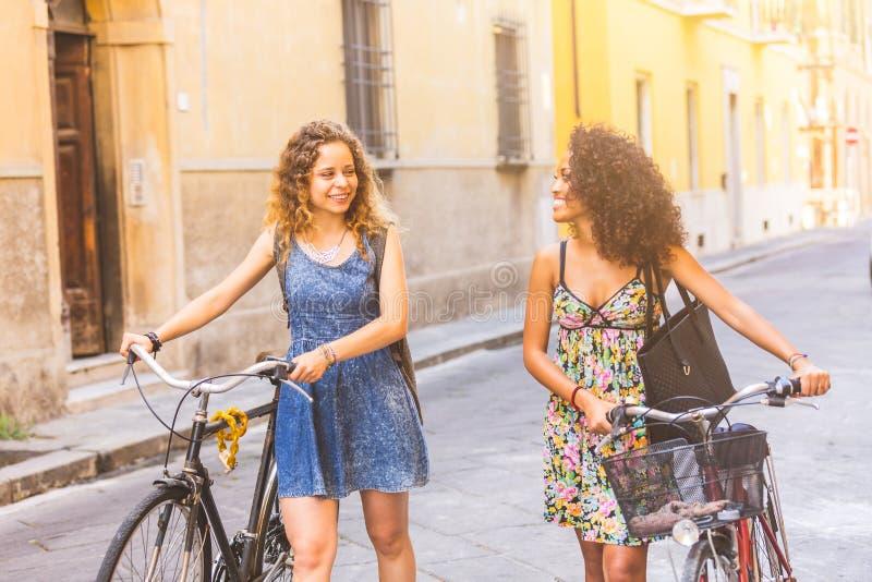 Coppie multirazziali degli amici con le bici nella città fotografia stock libera da diritti