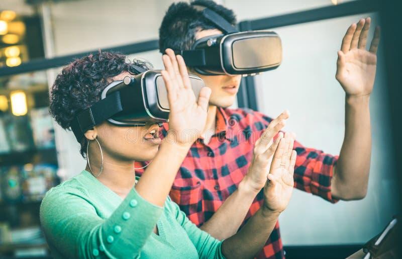 Coppie multirazziali nell'amore che gioca con gli occhiali di protezione di realtà virtuale del vr immagini stock