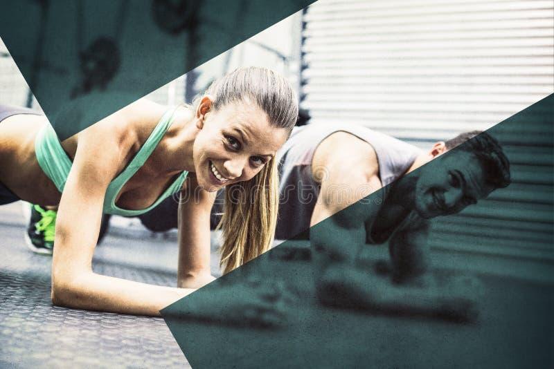 Coppie muscolari che fanno gli esercizi del tavolato fotografia stock libera da diritti