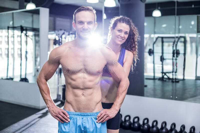 Coppie muscolari sorridenti che esaminano la macchina fotografica fotografia stock libera da diritti
