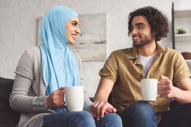 coppie musulmane sorridenti che si tengono per mano e che tengono le tazze di caffè fotografie stock