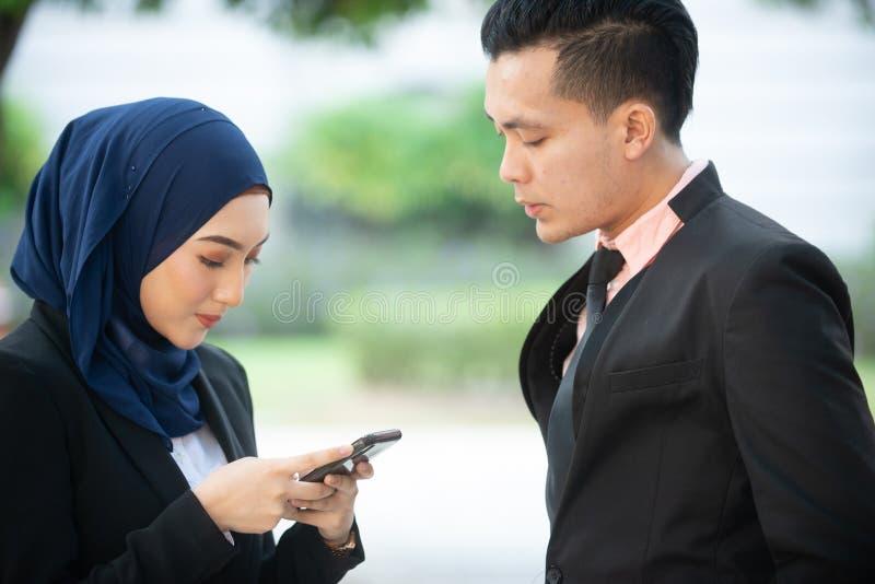 Coppie musulmane sul loro smartphone Mandando un sms e verificando ai loro media sociali fotografia stock