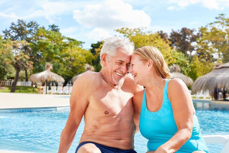 Coppie negli anziani di amore che godono della festa della stazione termale dallo stagno immagine stock libera da diritti