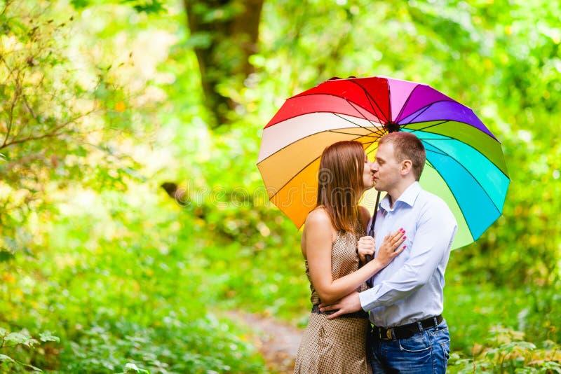 Coppie nei giovani di amore che si nascondono dalla pioggia sotto un ombrello fotografia stock