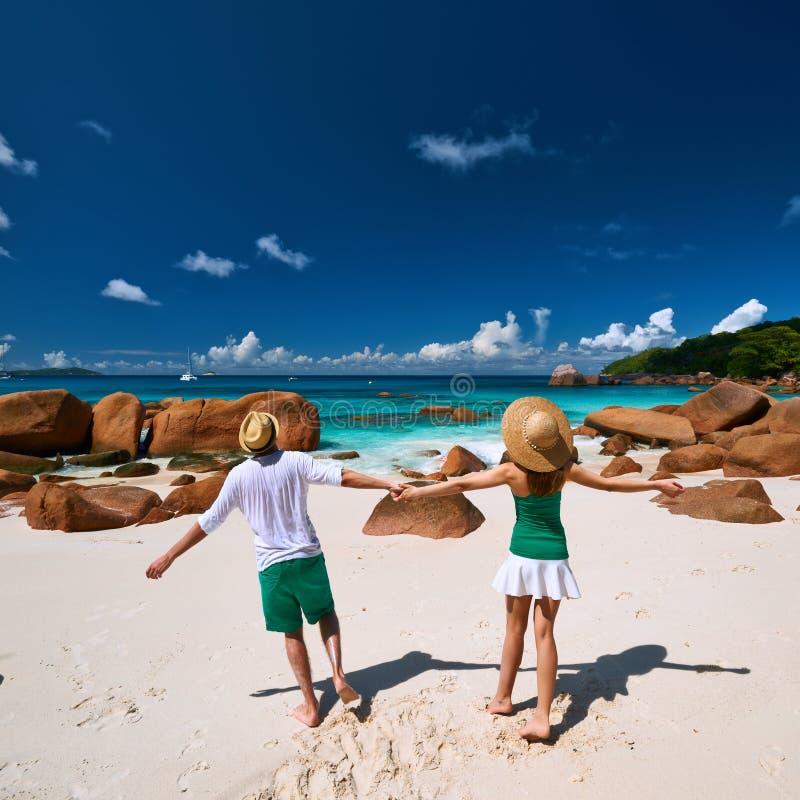 Coppie nel divertiresi verde su una spiaggia alle Seychelles fotografie stock
