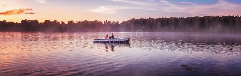 Coppie nel giro di amore in un'imbarcazione a remi sul lago durante il tramonto Tramonto romantico nell'ora dorata La donna e l'u immagine stock
