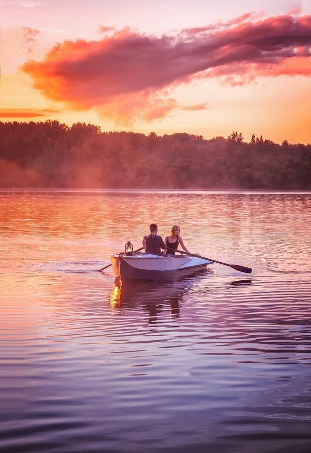 Coppie nel giro di amore in un'imbarcazione a remi sul lago durante il tramonto Tramonto romantico nell'ora dorata La donna e l'u fotografia stock libera da diritti
