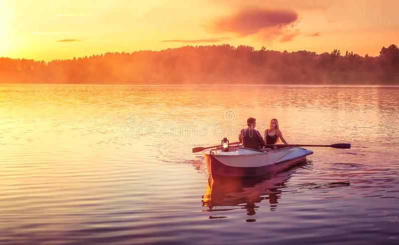 Coppie nel giro di amore in un'imbarcazione a remi sul lago durante il tramonto Tramonto romantico nell'ora dorata La donna e l'u immagini stock