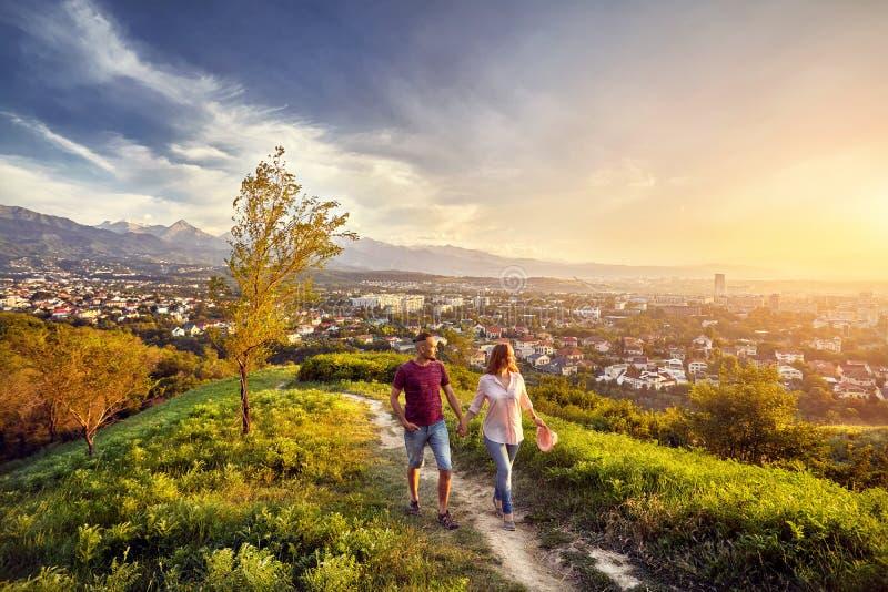 Coppie nel parco alla vista della città di tramonto fotografia stock