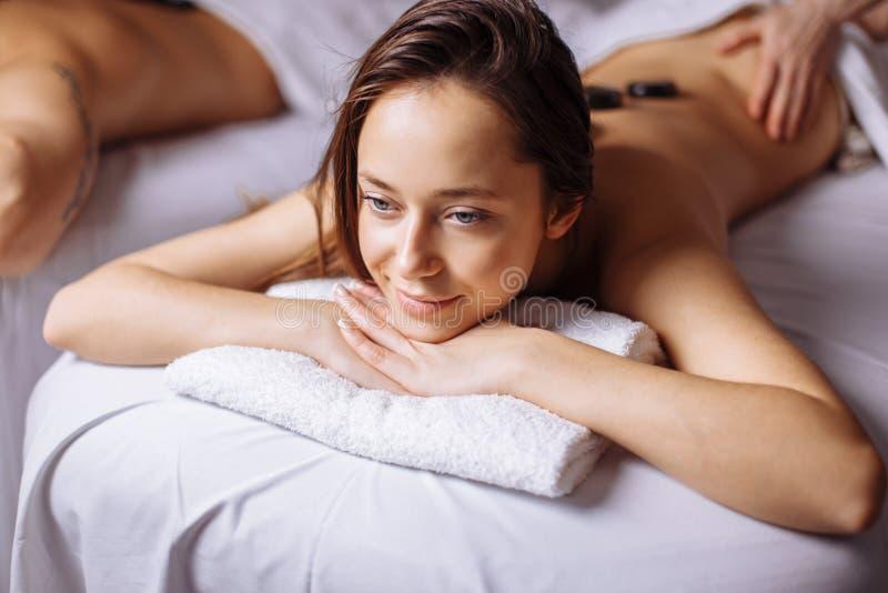 Coppie nel salone della stazione termale che ha massaggio di pietra caldo fotografie stock libere da diritti
