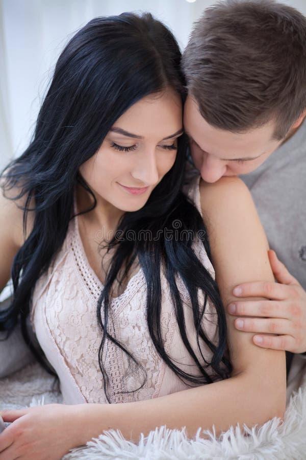 Coppie nell'amore che abbraccia e che bacia a casa fotografie stock