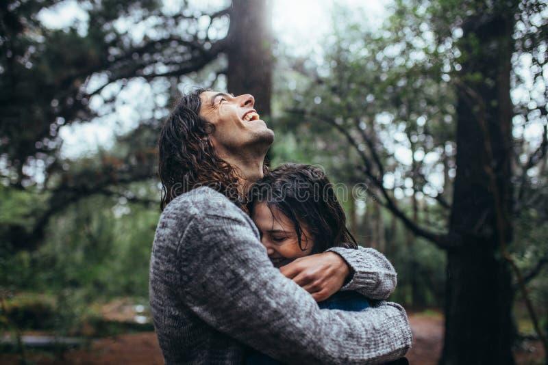 Coppie nell'amore che abbraccia nel parco sotto la pioggia fotografia stock