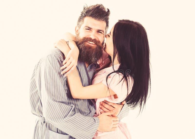Coppie nell'amore che abbraccia in pigiama, accappatoio Coppia stringere a sé, baciare della ragazza macho, isolato su fondo bian fotografie stock