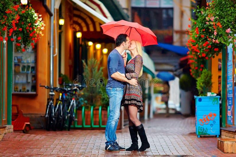 Coppie nell'amore che bacia sotto la pioggia fotografia stock libera da diritti