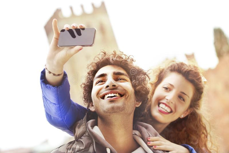 Coppie nell'amore che fa un selfie mentre lui gli che dà un bacio immagine stock