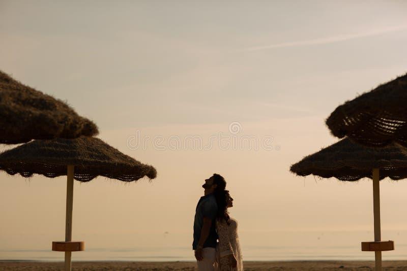 Coppie nell'amore che ha momenti teneri romantici sulla spiaggia vicino agli ombrelli di vimini Giovani amanti che godono delle v immagine stock libera da diritti