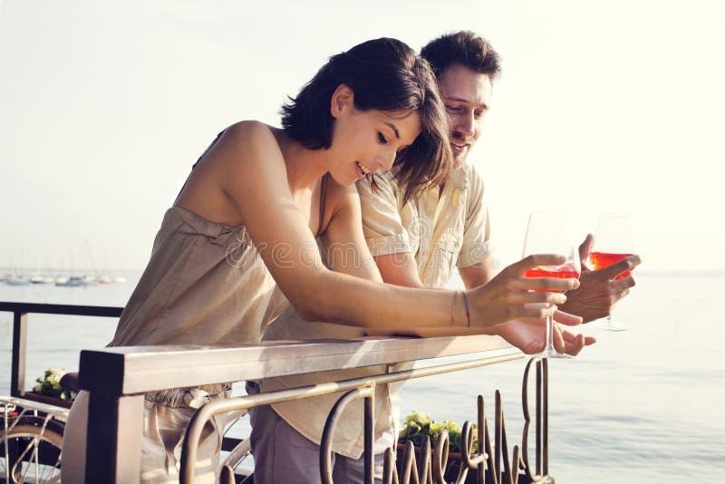 Coppie nell'amore che parla mentre hanno spritz in un terrazzo di vista del lago fotografia stock libera da diritti