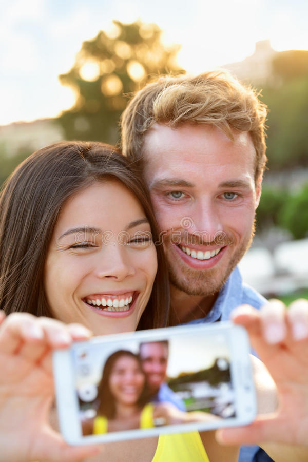 Coppie nell'amore che prende la foto del selfie con lo smartphone fotografie stock libere da diritti