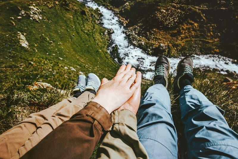 Coppie nell'amore che si tiene per mano rilassamento insieme sul summit della montagna fotografia stock libera da diritti