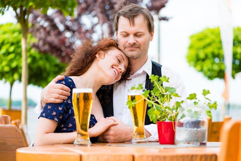 Coppie nell'amore che stringe a sé nel giardino della birra immagine stock libera da diritti