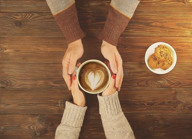 Coppie nell'amore che tiene tazza di caffè in mani su fondo di legno con la vista superiore dei biscotti fotografie stock