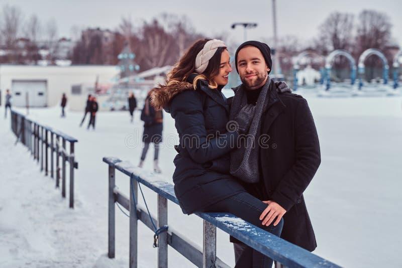 Coppie nell'amore, data alla pista di pattinaggio sul ghiaccio, una ragazza che si siede su una guardavia e che abbraccia con il  fotografia stock libera da diritti