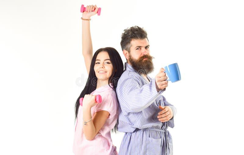 Coppie nell'amore in pigiama, supporto dell'accappatoio isolato su fondo bianco Concetto di alternativa di mattina Ragazza con il fotografia stock libera da diritti
