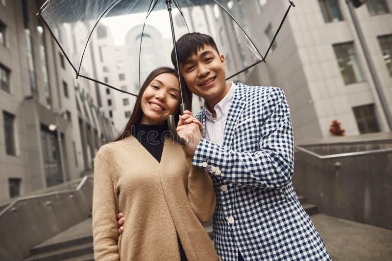 Coppie nell'amore sotto l'ombrello nel fondo del centro commerciale fotografia stock libera da diritti