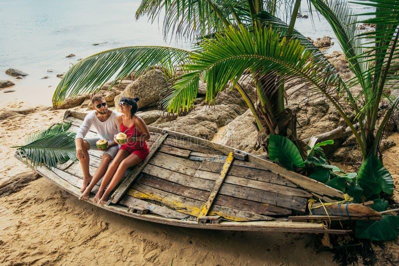 Coppie nell'amore sulla noce di cocco bevente della spiaggia fotografia stock libera da diritti