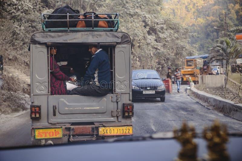 Coppie nell'automobile con gli effetti personali su funzionamento superiore sulla strada vicino a Bagdogra, Darjeeling, India fotografie stock libere da diritti