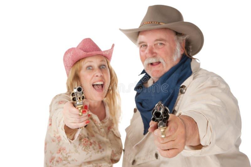 Coppie nell'usura occidentale che indica le pistole fotografie stock libere da diritti