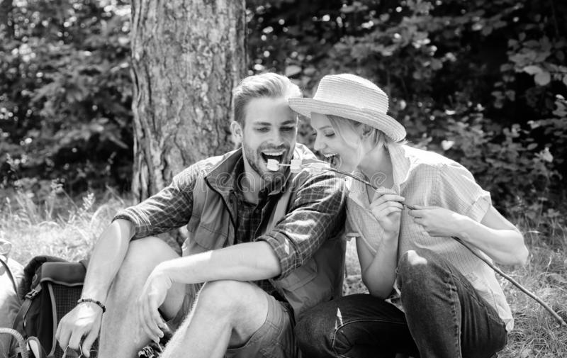Coppie nella foresta di campeggio di amore che mangia le caramelle gommosa e molle arrostite Attività di gruppo popolare delle ca fotografie stock libere da diritti