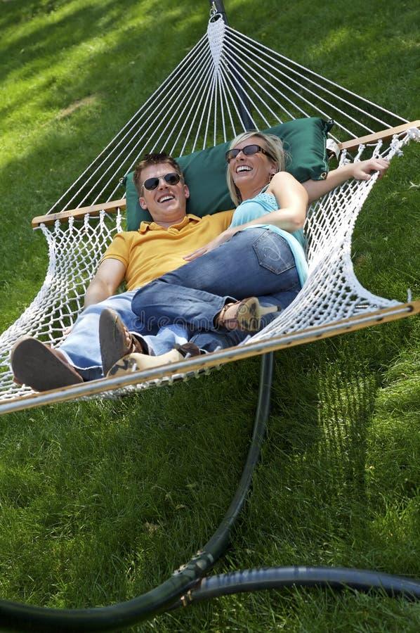 Coppie nella risata del hammock immagini stock libere da diritti