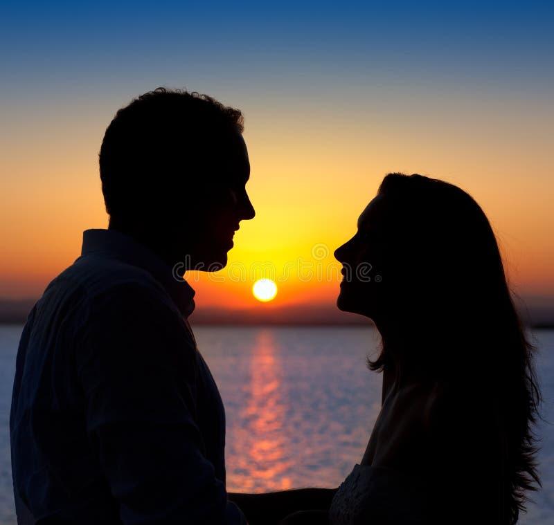 Coppie nella siluetta di amore al tramonto del lago fotografie stock libere da diritti