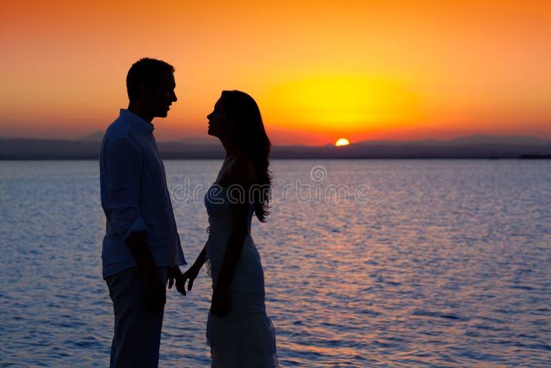 Coppie nella siluetta di amore al tramonto del lago immagine stock