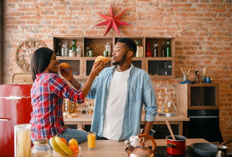Coppie nere allegre divertendosi sulla cucina fotografia stock