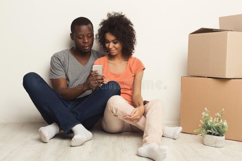 Coppie nere che si siedono sul pavimento al nuovo appartamento fotografia stock libera da diritti