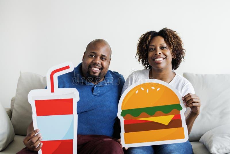 Coppie nere con le icone dell'alimento immagine stock libera da diritti