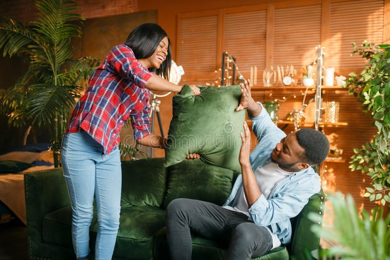 Coppie nere divertendosi sul sofà, lotta di cuscino immagine stock
