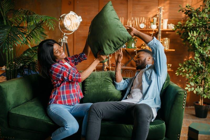 Coppie nere divertendosi sul sof?, lotta di cuscino fotografia stock libera da diritti