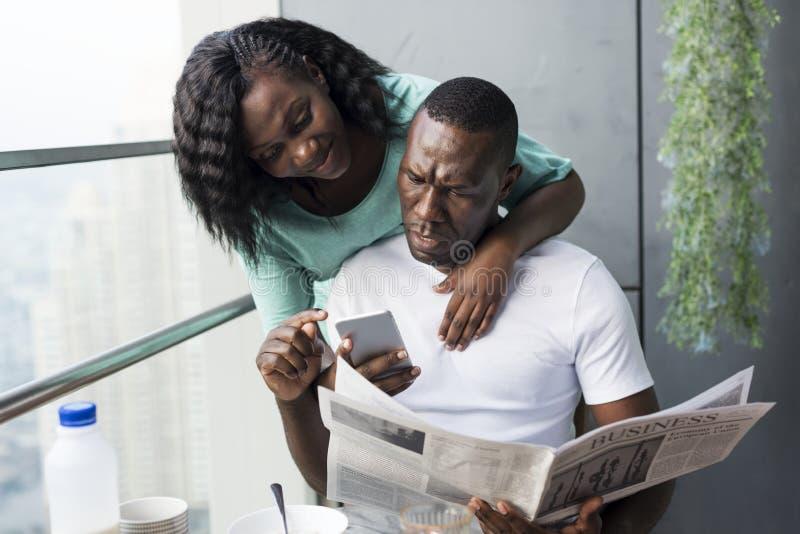 Coppie nere facendo uso del telefono cellulare immagine stock