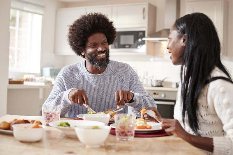 Coppie nere felici che godono mangiando la loro cena di domenica insieme a casa, fine su immagini stock