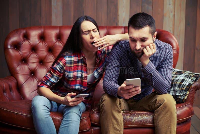 Coppie noiose che si siedono sul sofà immagini stock