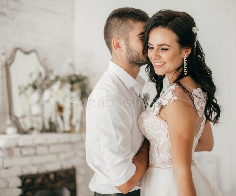 Coppie nuziali, donna felice della persona appena sposata ed uomo abbraccianti dentro alla camera da letto fotografie stock